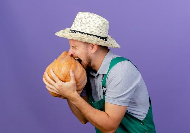 Jovem bonito jardineiro eslavo de uniforme e chapéu em pé na vista de perfil segurando e mordendo abóbora de butternut isolada