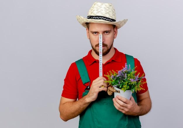 Jovem bonito jardineiro eslavo de uniforme e chapéu segurando fita métrica na frente do rosto olhando com um vaso de flores na outra mão isolado