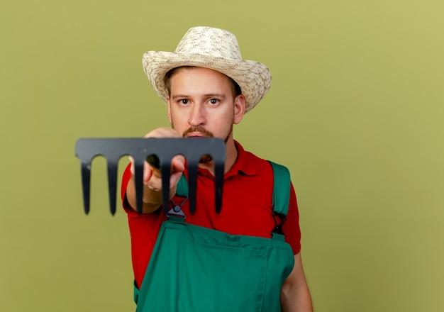 Jovem bonito jardineiro eslavo de uniforme e chapéu segurando o ancinho olhando e estendendo o ancinho para o isolado