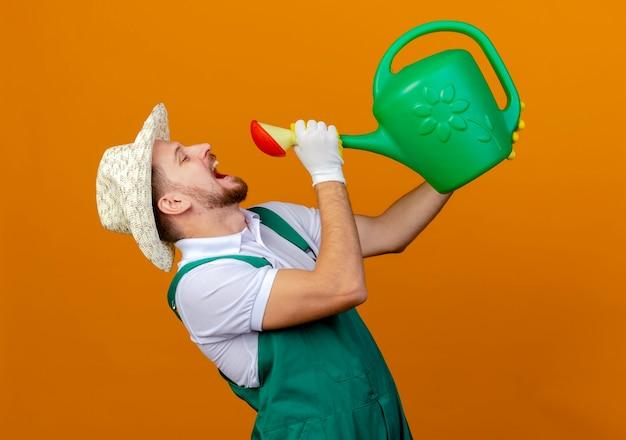 Jovem bonito jardineiro eslavo de uniforme, usando chapéu e luvas de jardinagem, bebendo água de um regador isolado
