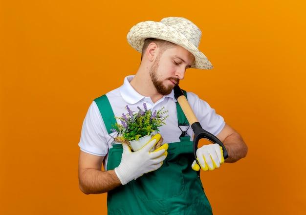 Jovem bonito jardineiro eslavo de uniforme, usando chapéu e luvas de jardinagem, segurando uma pá e um vaso de flores olhando a pá isolada
