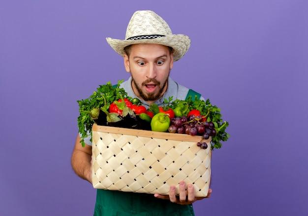 Jovem bonito jardineiro eslavo surpreso de uniforme e chapéu segurando e olhando para uma cesta de vegetais isolada