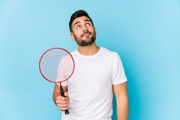 Jovem bonito jogando badminton isolado sonhando em alcançar objetivos e propósitos
