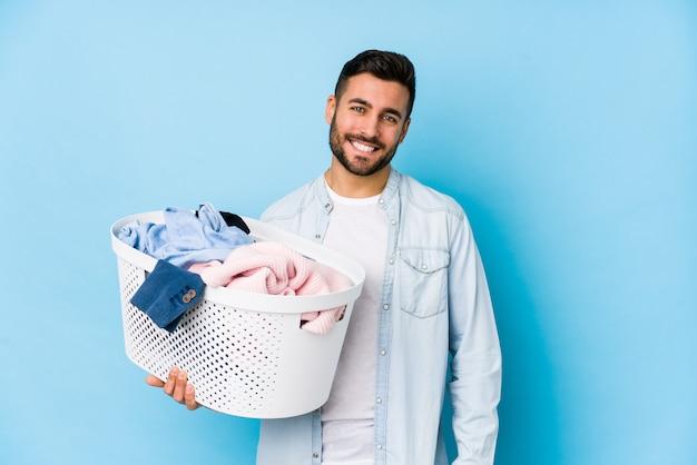Jovem bonito lavando roupa isolada feliz, sorridente e alegre