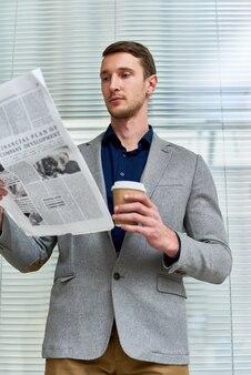 Jovem bonito lendo jornal no escritório
