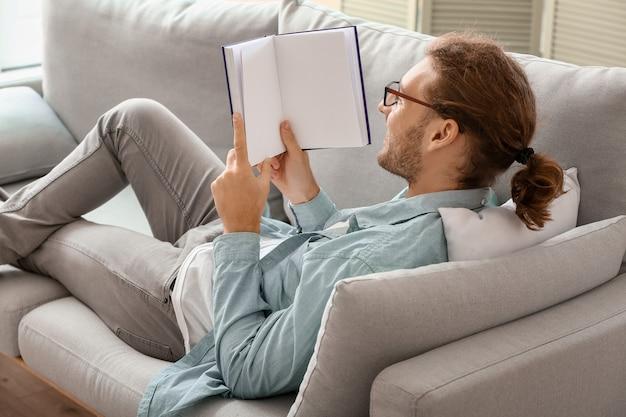 Jovem bonito lendo livro em casa
