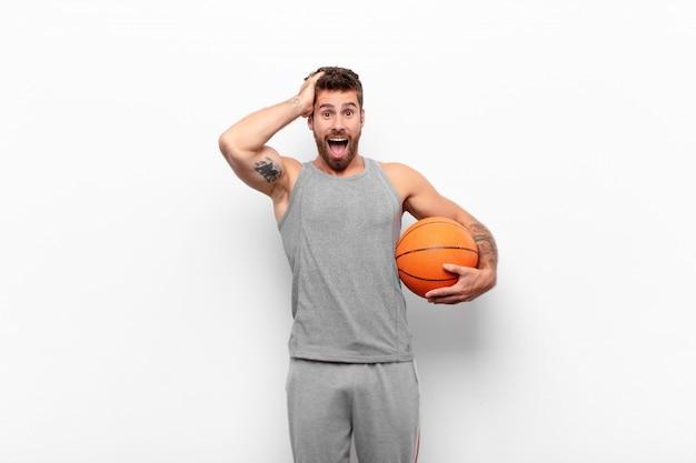 Jovem bonito, levantando as mãos na cabeça, boca aberta, sentindo-se extremamente sortudo, surpreso, animado e feliz, segurando uma bola de basquete.