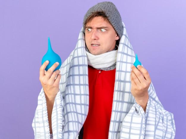 Jovem bonito loira doente, impressionado, usando chapéu de inverno e cachecol embrulhado em xadrez segurando enemas, olhando para um deles isolado no fundo roxo