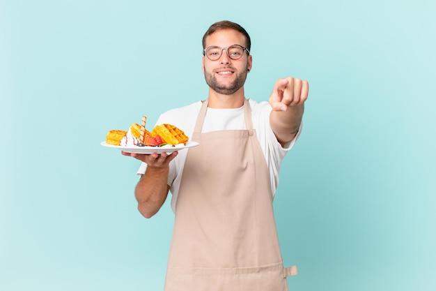 Jovem bonito loiro apontando para a câmera escolhendo você. cozinhar waffles conceito