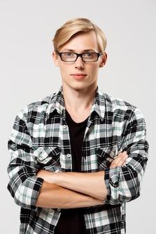 Jovem bonito loiro confiante em óculos, vestindo camisa xadrez casual com as mãos cruzadas no peito na parede cinza
