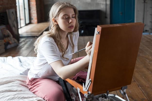Jovem, bonito, loiro, menina, com, escova, e, paleta, sentando, perto, cavalete, desenho, quadro, em, um, estúdio