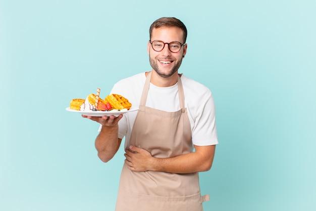 Jovem bonito loiro rindo alto de alguma piada hilária. cozinhar waffles conceito