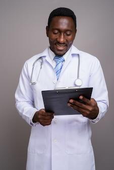 Jovem bonito médico africano contra um fundo cinza