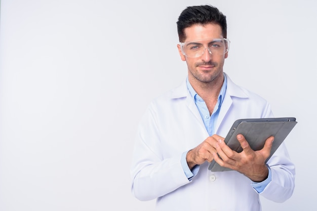 Jovem bonito médico usando óculos de proteção isolados contra uma parede branca
