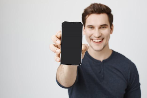 Jovem bonito mostrando a tela do celular