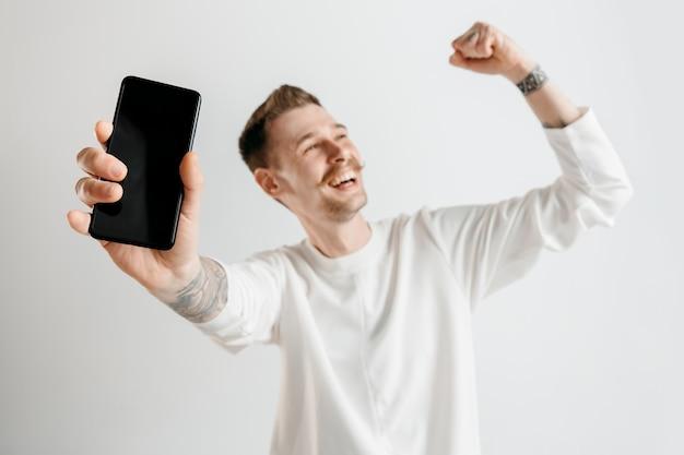 Jovem bonito mostrando a tela do smartphone cinza com uma cara de surpresa.