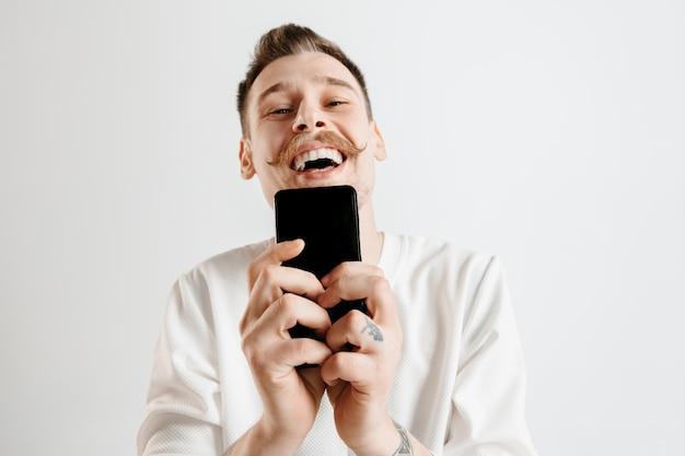 Jovem bonito mostrando a tela do smartphone sobre um fundo cinza com uma cara de surpresa. emoções humanas, conceito de expressão facial