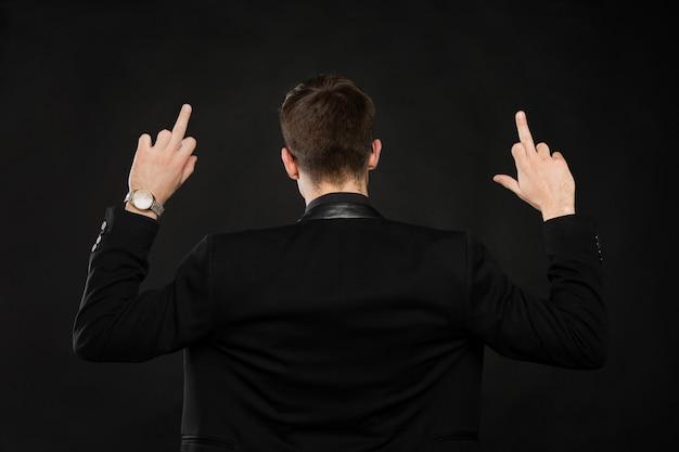 Jovem bonito mostrando dedo do meio, sinal de insulto na parede preta