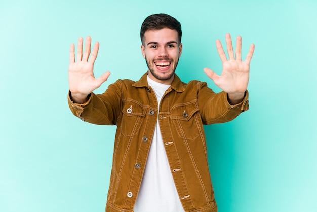 Jovem bonito mostrando o número dez com as mãos.