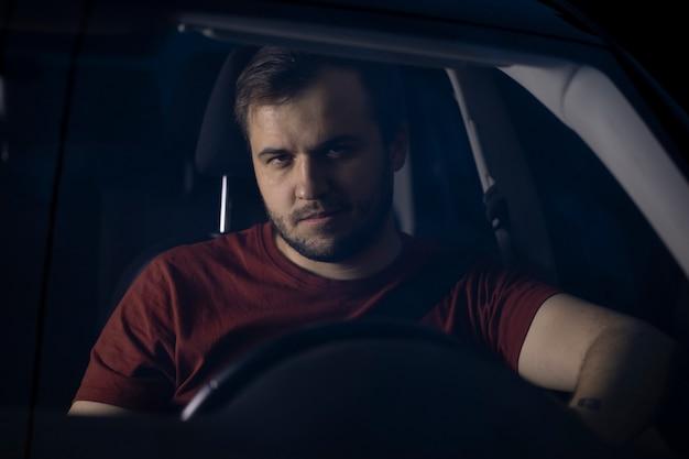 Jovem bonito motorista sentado ao volante do carro à noite, olhando para o futuro pensativamente