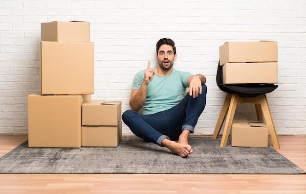Jovem bonito, movendo-se em nova casa entre caixas apontando com o dedo indicador uma ótima idéia