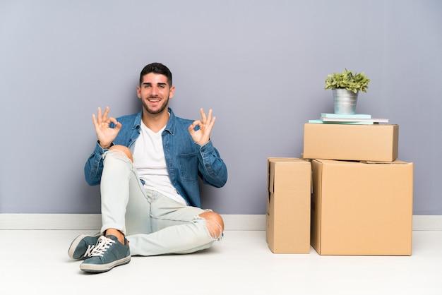 Jovem bonito, movendo-se em nova casa entre caixas mostrando um sinal de ok com os dedos