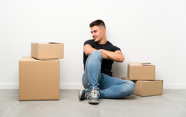 Jovem bonito, movendo-se em nova casa entre caixas, olhando para o lado
