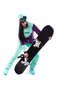 Jovem, bonito, mulher, em, roxo, traje esqui, segure snowboard