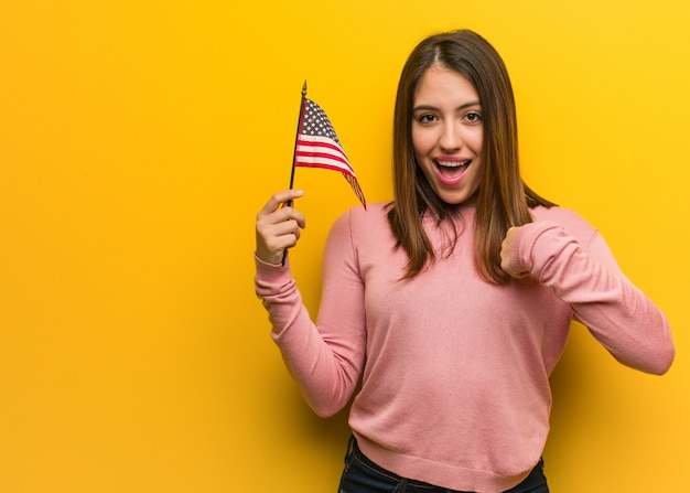 Jovem bonito mulher segurando uma bandeira dos estados unidos surpreendeu, sente-se bem sucedido e próspero