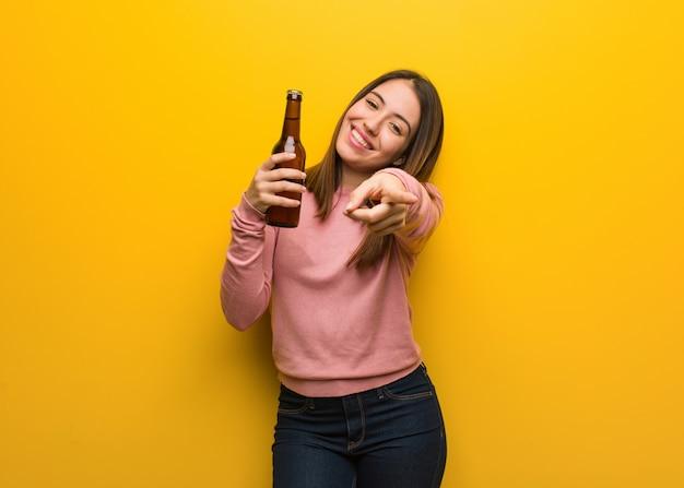 Jovem bonito mulher segurando uma cerveja alegre e sorrindo apontando para frente