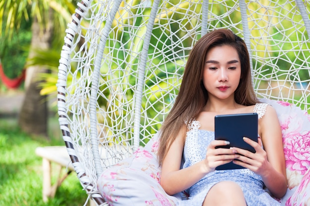 Jovem, bonito, mulher, sentando, uso, laptop, em, balanço
