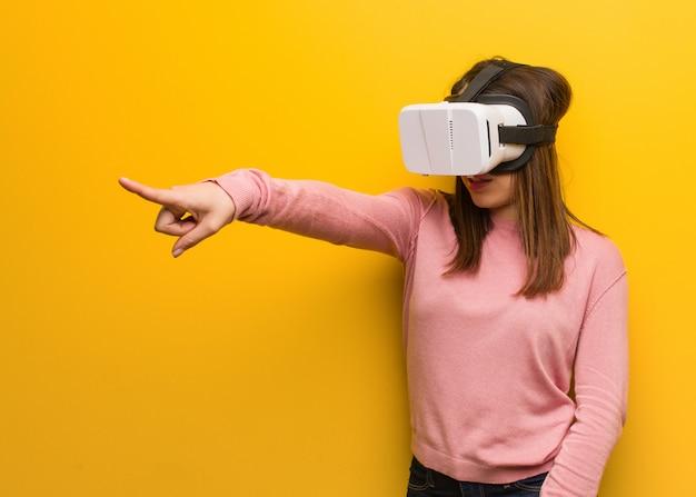 Jovem bonito mulher usando uma realidade virtual googles alegres e sorrindo apontando para frente