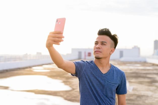 Jovem bonito multi étnica tomando selfie no telhado do edifício