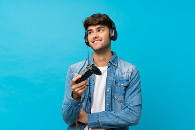 Jovem bonito muro azul isolado jogando em videogame