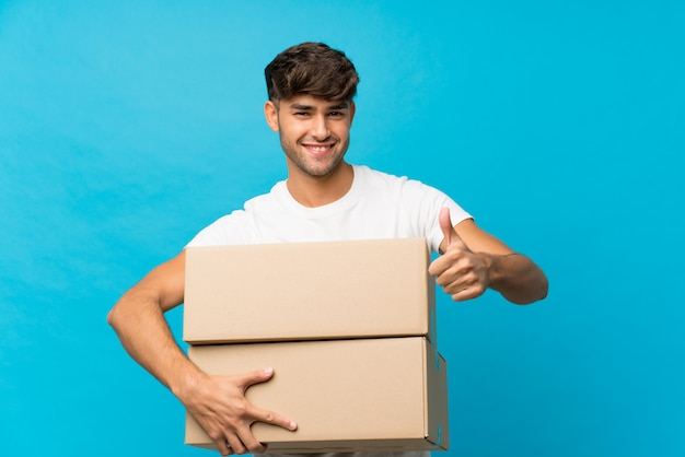 Jovem bonito muro azul isolado, segurando uma caixa para movê-lo para outro site com o polegar para cima