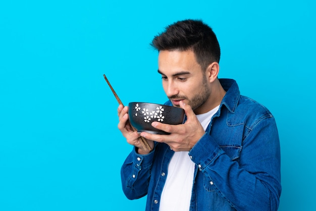Jovem bonito muro azul isolado, segurando uma tigela de macarrão com pauzinhos e comê-lo
