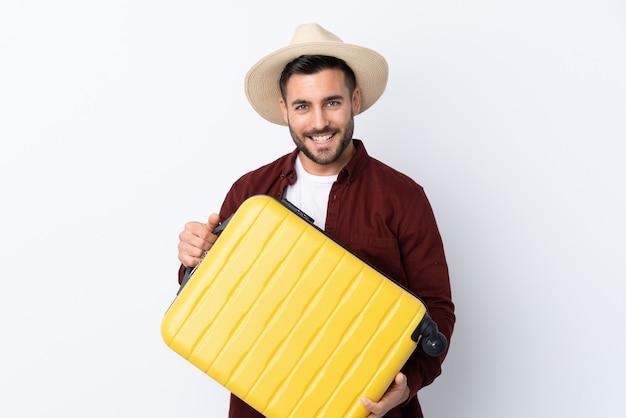 Jovem bonito muro branco isolado em férias com mala de viagem e um chapéu