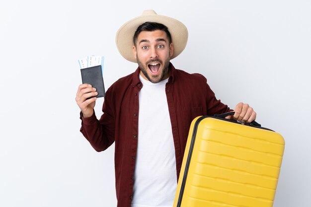 Jovem bonito muro branco isolado em férias com mala e passaporte e surpreso