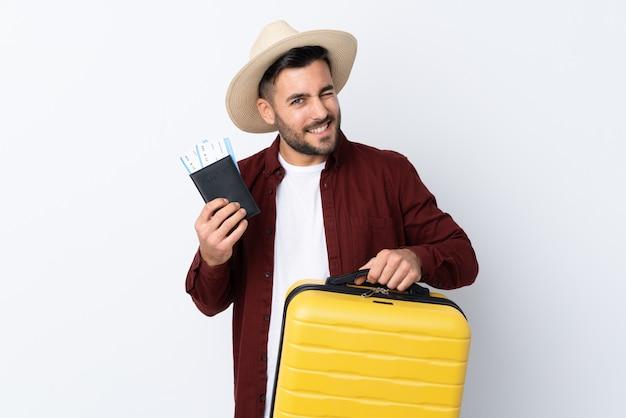 Jovem bonito muro branco isolado em férias com mala e passaporte