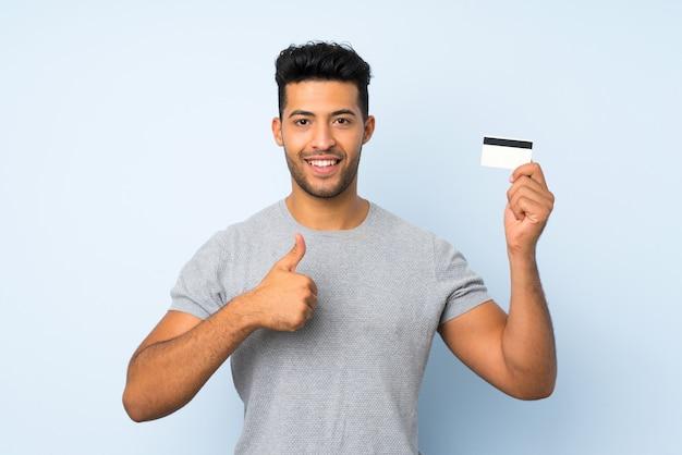 Jovem bonito muro isolado segurando um cartão de crédito