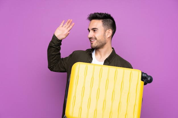 Jovem bonito muro roxo isolado em férias com mala de viagem e saudando