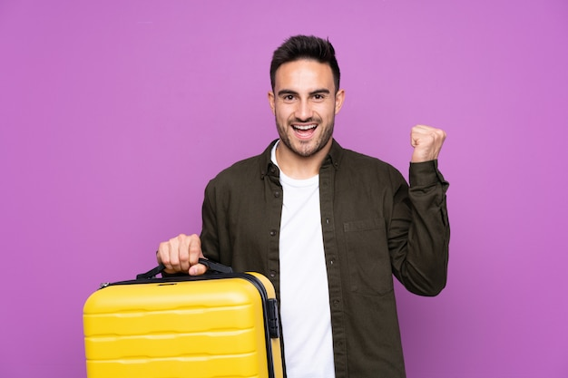 Jovem bonito muro roxo isolado em férias com mala de viagem e um chapéu
