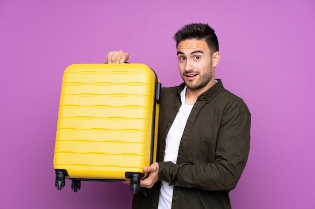 Jovem bonito muro roxo isolado em férias com mala de viagem