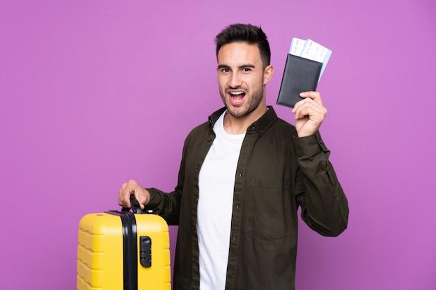 Jovem bonito muro roxo isolado em férias com mala e passaporte