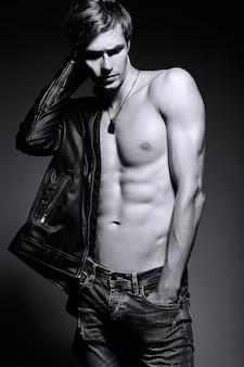 Jovem bonito musculoso cabe homem modelo masculino na jaqueta de couro posando no estúdio, mostrando seus músculos abdominais