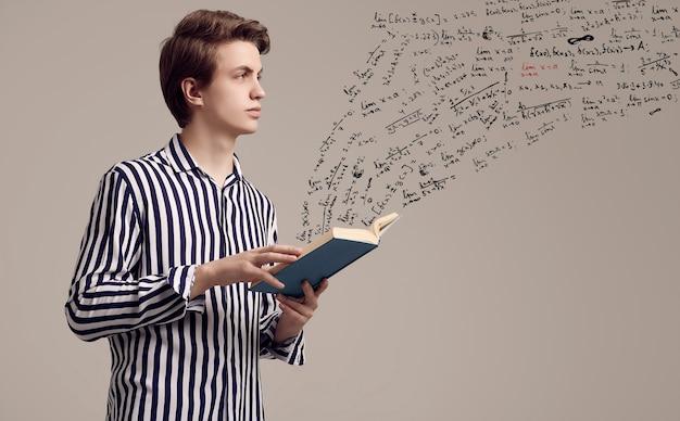 Jovem bonito na camisa listrada, lendo um livro sobre fundo cinza