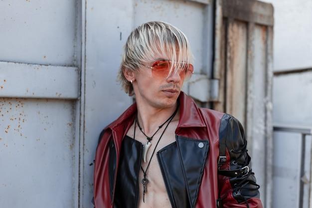 Jovem bonito na jaqueta de couro preta e vermelha da moda em óculos de sol vermelhos com penteado elegante ao ar livre perto da parede cinza metálica.
