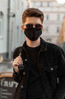 Jovem bonito na moda em óculos de sol da moda em roupas jeans elegantes e máscara médica preta caminha ao ar livre ao pôr do sol