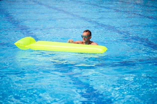 Jovem bonito nadando em colchão inflável na piscina azul