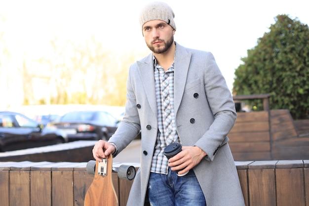 Jovem bonito no casaco cinza e chapéu, bebendo café, descansando, em pé com longboard. conceito de skate urbano.